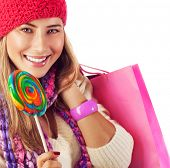 foto of goodies  - Image of nice blond girl wearing warm winter red hat and eating tasty sugar candy - JPG