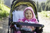 stock photo of buggy  - Smiling pretty little child girl in buggy on nature - JPG