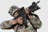 stock photo of corps  - US Marine Corps soldier aiming assault rifle against gray background - JPG