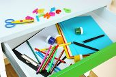 School supplies in open desk drawer close up