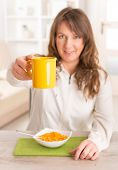Beautiful young woman eating cornflakes and holding cup of coffee at home