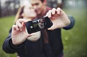 foto of two women taking cell phone  - Romantic teenage couple taking self portrait with cell phone at the park. 