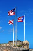 Puerto Rico state, US national and San Juan city flag fly with blue sky in San Juan El Morro castle.