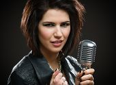 Portrait of female rock singer wearing black jacket and keeping microphone on grey background. Conce