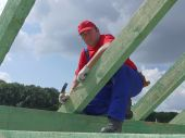 image of purlin  - Roofer posing on house rafter beam against the sky - JPG