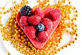 foto of hackney  - Heart shaped cake with berries on top and with a gold beads - JPG