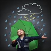 stock photo of lightning  - Young happy child singing and dancing holding an umbrella standing in front of a chalk drawing of a rain and lightning storm on a school blackboard - JPG