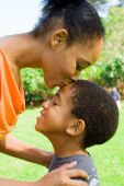 picture of happy kids  - happy african american mother kissing son outdoors - JPG