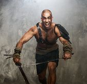 foto of legion  - Wounded gladiator with  two swords covered in blood - JPG
