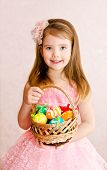 stock photo of human egg  - Smiling little girl with basket full of colorful easter eggs - JPG