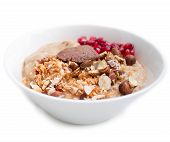 stock photo of porridge  - Bowl of oatmeal porridge with pomegranates walnuts almonds coconut flakes apple sauce and hazelnut butter isolated on white