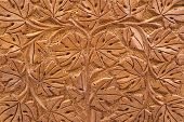 picture of woodcarving  - Closeup of brown woodcarving of branches and leaves in geometric design - JPG
