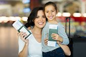 pic of boarding pass  - beautiful mother and daughter holding passports and boarding pass at airport - JPG