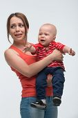 stock photo of fussy  - Portrait of young attractive mother holding her screaming toddler son being naughty and cranky - JPG