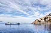 stock photo of hydra  - Aegean Sea and Greek island of Hydra or Ydra a ship and a dramatic blue and white cloudy sky in the Saronic Gulf Aegean Sea Greece.