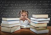 stock photo of pews  - Sad tired busy little girl with big eyes wearing glasses sitting in the pew next to her many many books - JPG