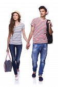 stock photo of girl walking away  - Full length of young couple walking with travel bags with joined hands looking way at copy space - JPG
