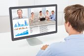 stock photo of entrepreneurship  - Rear view of businessman video conferencing on computer at desk in office - JPG