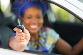 stock photo of zulu  - african zulu woman showing car key inside new vehicle - JPG