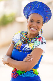 stock photo of zulu  - young south african zulu woman in traditional clothes portrait outdoors - JPG