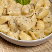 foto of shredded cheese  - Italian tortellini pasta with cheese sauce and basil - JPG
