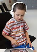 pic of classroom  - Child boy with headphones listening music or audio in a classroom or library room - JPG
