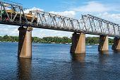 stock photo of railcar  - Petrivskiy railroad bridge in Kyiv across the Dnieper with freight train on it - JPG