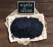 stock photo of cumin  - Plie of Nigella sativa or Black cumin on a wooden table - JPG