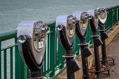 picture of binoculars  - Row of vending tourist binoculars along riverfront - JPG