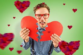stock photo of heartbreaking  - Geeky hipster holding a broken heart against green vignette - JPG