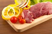 stock photo of pork chop  - raw pork meat with vegetable on chopping block - JPG