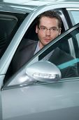image of showrooms  - Car salesperson getting in car at showroom - JPG
