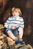 stock photo of denim wear  - Cute little blond boy sitting on cut wood and leaning on an old wooden wall - JPG
