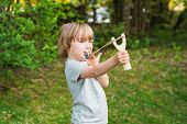 picture of mischief  - Cute little boy playing with slingshot - JPG
