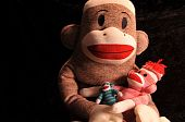 stock photo of sock-monkey  - three various sized sock monkeys in a pose the way a child would hold a doll - JPG