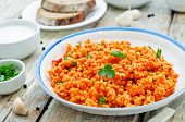 picture of millet  - millet porridge with tomato sauce garlic and parsley on a white wood background - JPG