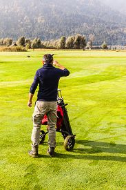 stock photo of golf bag  - a golf player choosing a golf club from the golf bag in a beautiful golf course - JPG
