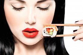 foto of japanese woman  - Fashion art portrait of beauty model girl eating Sushi roll - JPG