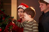pic of nuclear family  - Family looking at christmas tree at home celebrating together - JPG