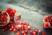 Постер, плакат: Pomegranate Oil In Bottle And Garnet Fruit With Seeds On Table