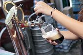 stock photo of guinness  - Pouring dark beer to plastic glass from beer tap - JPG