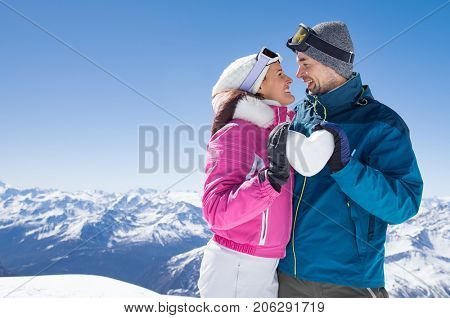 poster of Young couple looking at each other and holding snow heart. Smiling man and woman in winter clothing