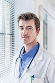 Close-up portrait of a young serious doctor looking at camera with determination and dedication in a poster