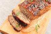 Tasty baked turkey meatloaf on wooden board poster