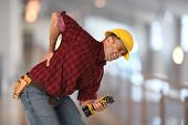 Worker experiencing sharp back pain while holding drill inside building poster