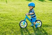 Boy in helmet riding a blue balance bike (run bike). Happy child learning to keep balance on a train poster