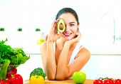 Beauty young Funny woman holding fresh avocado. vegetables, tomatoes. Smiling in her kitchen. Health poster