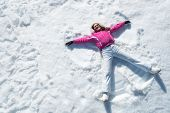 High angle view of happy woman lying on snow and moving her arms and legs up and down creating a sno poster
