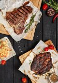 Постер, плакат: Gourmet Grill Restaurant Steak Menu T Bone and Rib Eye Beef Steak on Black Wooden Background Blac