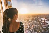 Europe travel woman looking at sunset view of London city skyline from the window of highrise skyscr poster